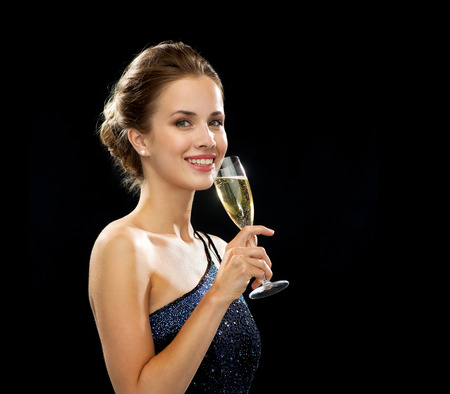 party, drinks, holidays, luxury and celebration concept - smiling woman in evening dress with glass of sparkling wine over black background photo