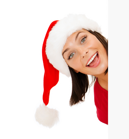 christmas, xmas, holidays and advertisement concept - happy woman in santa helper hat peeking out from blank white board photo