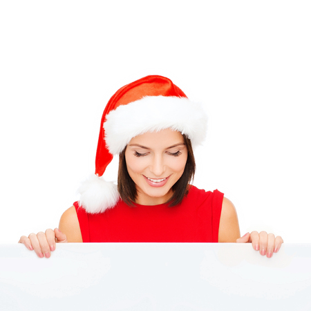 christmas, xmas, holidays and advertisement concept - happy woman in santa helper hat with blank white board photo
