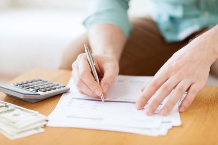 COnomie, finances, économie et concept de la maison - gros plan de l'homme avec la calculatrice, compter l'argent et prendre des notes à la maison Banque d'images - 31412046