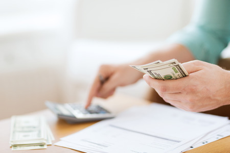 business savings: savings, finances, economy and home concept - close up of man with calculator counting money and making notes at home