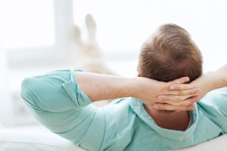 descansando: hogar, ocio, relax y felicidad concepto - hombre tumbado o sentado en el sofá en casa de atrás