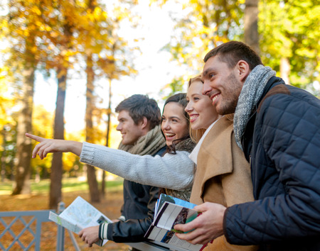 travel, people, tourism, gesture and friendship concept - group of smiling friends with map standing on bridge and pointing finger in city park photo