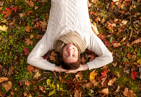 lying on leaves: season, happiness and people concept - smiling young man lying on ground or grass and fallen leaves in autumn park