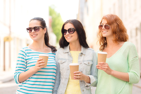 vacation, weekend, drinks and friendship concept - smiling teenage girls with coffee cups on street photo