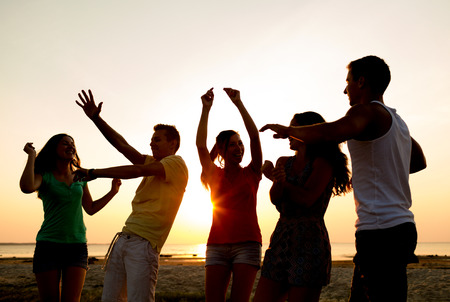 friendship, summer vacation, holidays, party and people concept - group of smiling friends dancing on beach photo