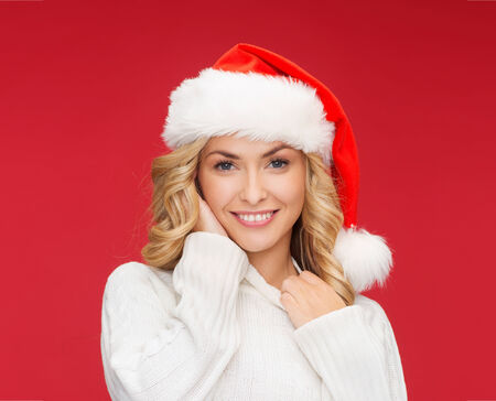 christmas, x-mas, winter, happiness concept - smiling woman in santa helper hat photo