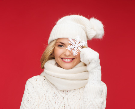 winter, people, happiness concept - woman in hat, muffler and gloves with big snowflake Stock Photo