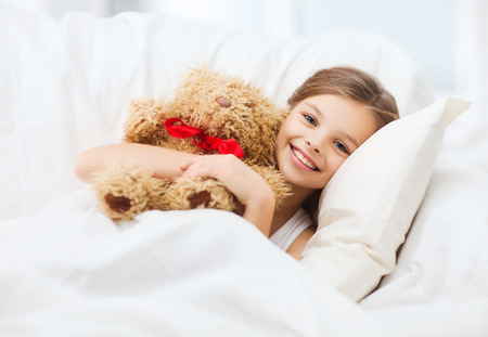 health and beauty concept - little girl with teddy bear sleeping at home photo