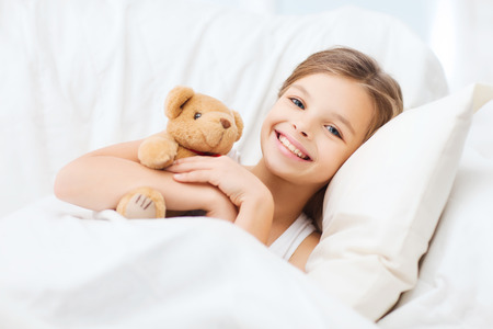 child in bed: health and beauty concept - little girl with teddy bear sleeping at home