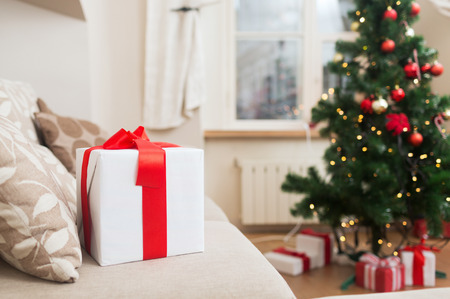 christmas spirit: christmas, x-mas, holidays, winter and happiness concept - gift box on coach at home