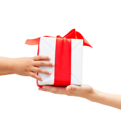 holidays, present, christmas, childhood and happiness concept - close up of child and mother hands with gift box Stock Photo