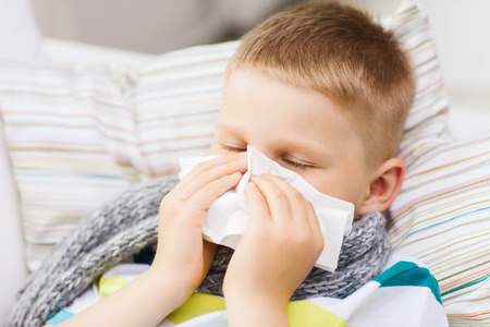 grippe: childhood, healthcare and medicine concept - ill boy with flu blowing nose at home Stock Photo