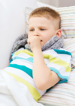 grippe: childhood, healthcare and medicine concept - ill boy with flu coughing at home Stock Photo