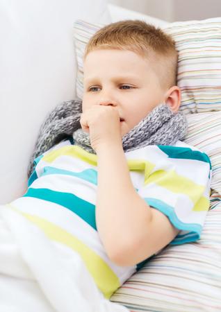 tosiendo: la infancia, la salud y la medicina concepto - muchacho enfermo con gripe tose en casa Foto de archivo