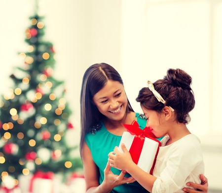 asian trees: holidays, presents, christmas, x-mas concept - happy mother and child girl with gift box