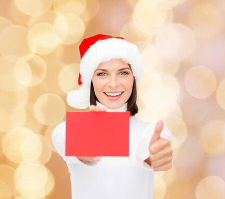 christmas, holdays, people, advertisement and sale concept - happy woman in santa helper hat with blank red card showing thumbs up gesture over beige lights background photo