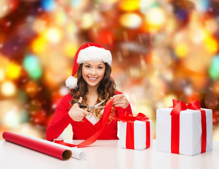 christmas, holidays, celebration, decoration and people concept - smiling woman in santa helper hat with scissors packing gift box over red lights background photo