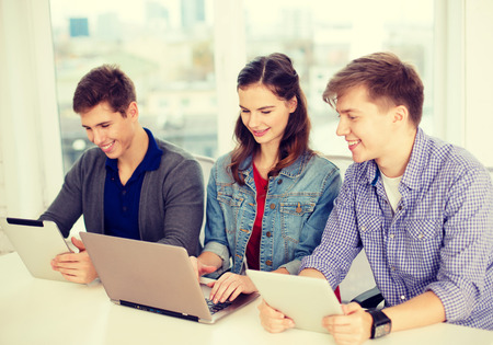 education, technology, school and internet concept - three smiling students with laptop and tablet pc at school Stock Photo