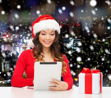 christmas, holidays, technology and people concept - smiling woman in santa helper hat with gift box and tablet pc computer over snowy night city background photo