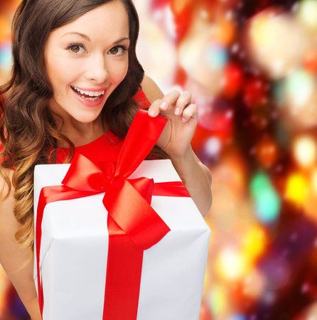 christmas, x-mas, valentines day, celebration concept - smiling woman in red dress with gift box photo