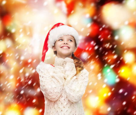 christmas, x-mas, winter, happiness concept - dreaming girl in santa helper hat photo