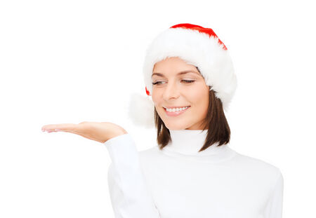 christmas, xmas, winter, happiness concept - smiling woman in santa helper hat with something on palm photo