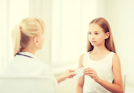 doctor giving pills: healthcare and medical concept - doctor giving tablets to child in hospital