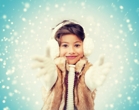 winter clothes: winter, people, happiness concept - happy little girl in winter clothes