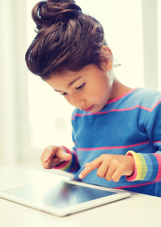 education, technology and internet concept - little girl with tablet pc photo
