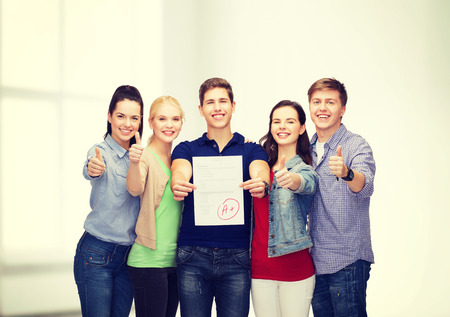 high class: education and people concept - group of smiling students standing and showing test and thumbs up