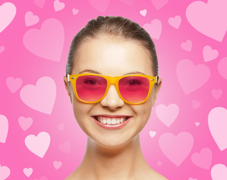 love, happiness, valentines day, face expressions and people concept - portrait of smiling teenage girl in pink sunglasses over background with hearts photo