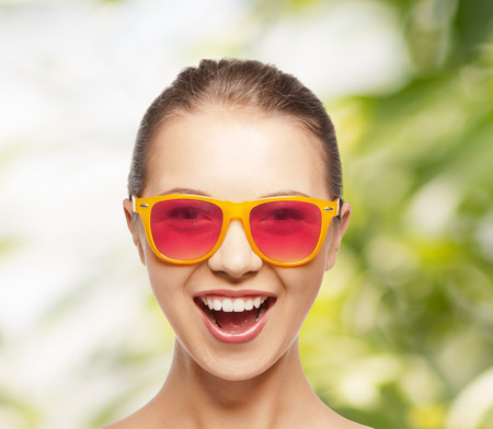 sweet smile: happiness and people concept - portrait of happy teenage girl in pink sunglasses
