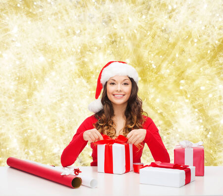 christmas, holidays, celebration, decoration and people concept - smiling woman in santa helper hat with decorating paper packing gift boxes over yellow lights background photo
