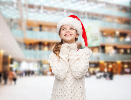 christmas, holidays, childhood and people concept - smiling girl in santa helper hat over shopping center background photo