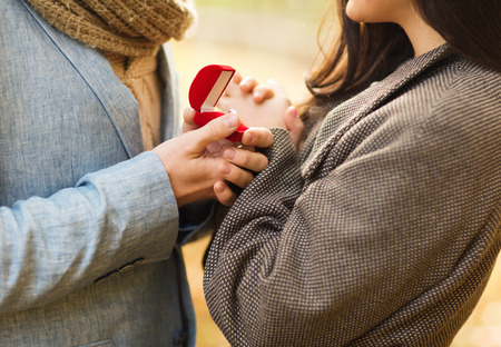 marry: love, relationship, family and people concept - close up of couple with red gift box in autumn park Stock Photo