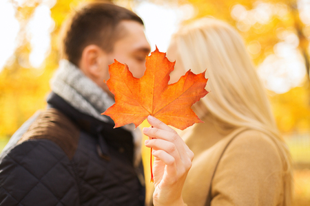 love, relationship, family and people concept - close up of couple with maple leaf kissing in autumn park photo