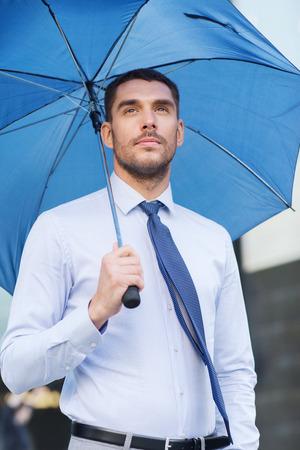 UOMO pioggia: affari, maltempo e le persone e il concetto - giovane uomo d'affari serio con ombrello all'aperto Archivio Fotografico