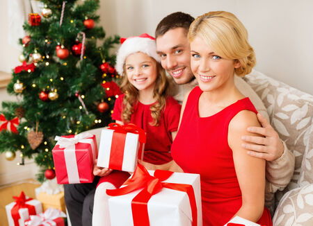 papa noel: family, christmas, x-mas, happiness and people concept - smiling family in santa helper hats with many gift boxes