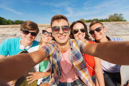 out in town: friendship, leisure, summer, technology and people concept - group of smiling friends with skateboard making selfie outdoors Stock Photo