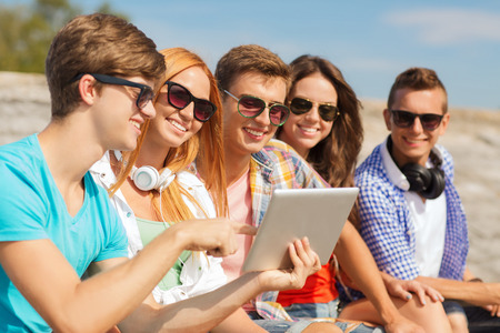 young people fun: friendship, leisure, summer and people concept - group of smiling friends with tablet pc computer sitting outdoors
