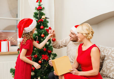 decorating christmas tree: family, christmas, x-mas, happiness and people concept - smiling family in santa helper hats decorating christmas tree Stock Photo