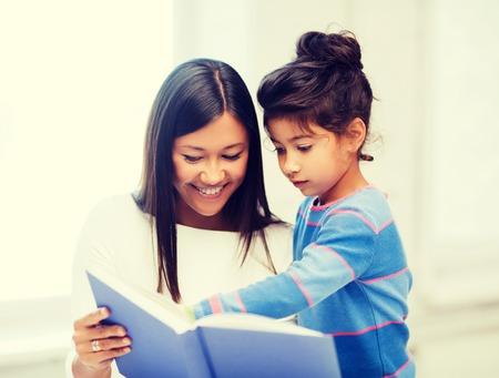 concept van familie, kinderen, onderwijs, school en gelukkige mensen - moeder en dochter met boek