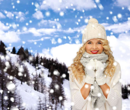 head wear: happiness, winter holidays, tourism, travel and people concept - smiling young woman in white hat and mittens over snowy mountains background Stock Photo
