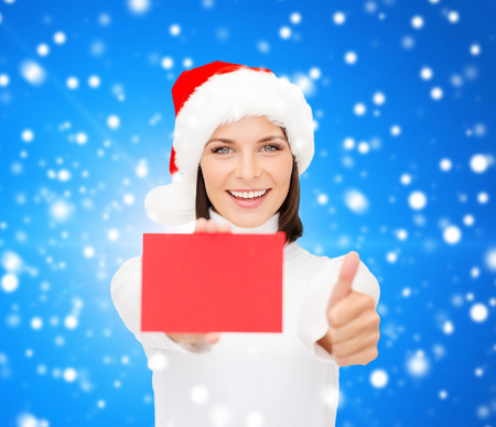 christmas, holdays, people, advertisement and sale concept - happy woman in santa helper hat with blank red card showing thumbs up gesture over blue snowy background photo