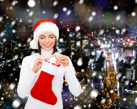 christmas sock: christmas, winter, happiness, holidays and people concept - smiling woman in santa helper hat with small gift box and stocking over snowy night city background