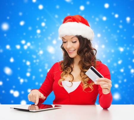 christmas, holidays, technology and shopping concept - smiling woman in santa helper hat with credit card and tablet pc computer over blue snowy background photo