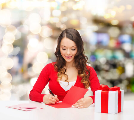 christmas, holidays, celebration, greeting and people concept - smiling woman with gift box writing letter or sending post card over lights background photo