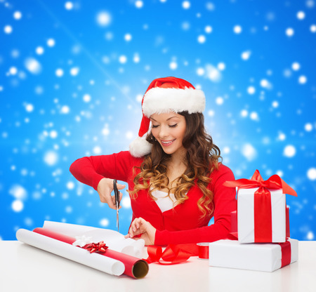 christmas, holidays, celebration, decoration and people concept - smiling woman in santa helper hat with scissors packing gift box over blue snowy background photo