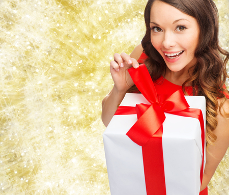 fancy box: christmas, holidays, valentines day, celebration and people concept - smiling woman in red dress with gift box over yellow lights background Stock Photo